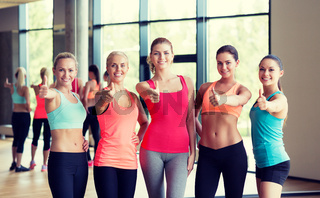 group of women showing thumbs up gesture in gym