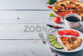Frittata with chorizo, tomatoes and chili on plate and coffee.