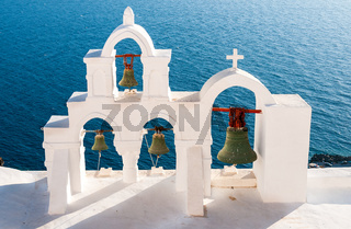 Traditional white christian church belfry with bells. Santorini island in Greece