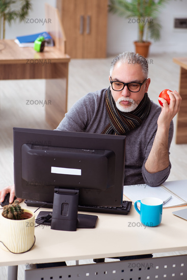 Old male employee working from house during pandemic