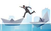 Businessman escaping sunken paper boat ship