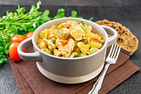 Chicken with vegetables and peas in saucepan on dark board