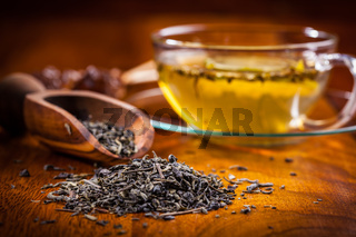 Dry green tea on wooden table