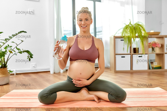 pregnant woman drinking water after yoga at home