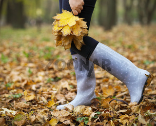 Woman having fun with yellow maple leaves