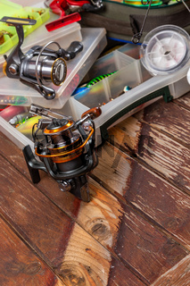 Different fishing tacles with rod and reels on wooden brown background.