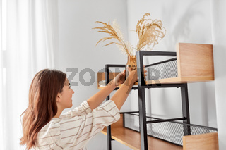 woman decorating home with dried flowers in vase