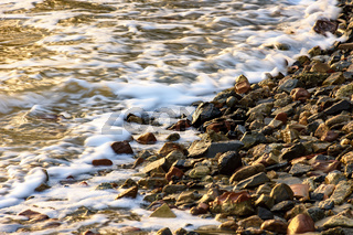 Small stones on the shore with the foam
