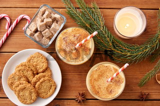 glasses of eggnog, oatmeal cookies and fir branch