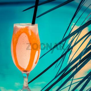 Orange Mango Smoothie Beside a Cyan Resort Swimming Pool