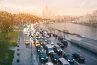 Daytime traffic of cars in Moscow. Light from headlights of cars and buildings. The movement of cars in the city center. Blurred background and rainy weather