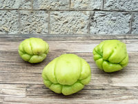 Three fruits of chayote on wood in front of a wall