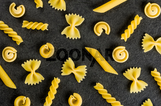Different types of pasta on a slate background