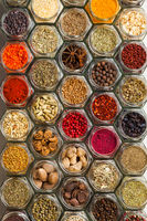 Top view of colourful spices in bottles like a pattern