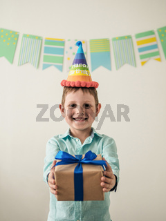 Five year old boy in his birthday hold gift box