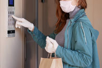 Courier's hands in black medical gloves deliver parcels in paper bag to the door during the epidemic coronovirus, COVID-19. Safe delivery online orders during epidemic.