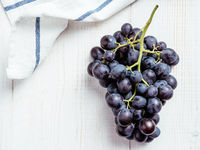 Dark grape bunch on white wooden table