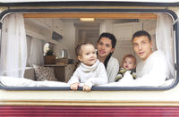 Portrait of the smiling happy family with kids in the house on wheels