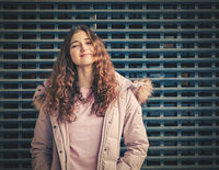 Redhead lady with wavy hair poses in a jacket in front of a metal fence mesh. She puts her chin slightly up in the camera with confidence.