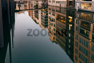 Scenic view of reflections of buildings and lights on water at Bleichenfleet canal in Hamburg