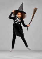 girl in black witch hat with broom on halloween