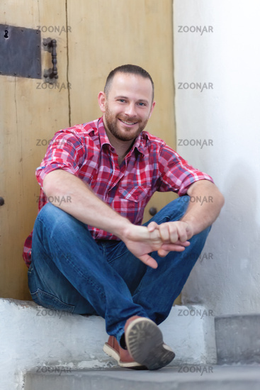 young bearded man sitting at a door