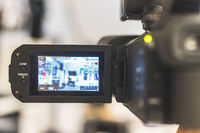 Professional film production: Male filmmaker is recording with a professional movie camera. Close up of camera lcd screen