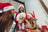 Several girls play with a small dog on New Years Eve