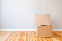 two cardboard boxes in empty room with wall background and copy space, moving in new flat concept mockup