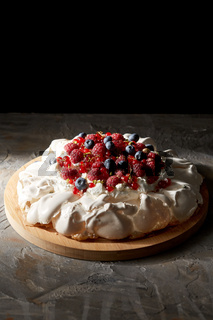 pavlova meringue cake with berries on wooden board