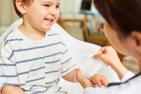 Kinderarzt bindet Mullbinde um Handgelenk von Kind