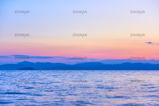 Colorful view of the sea and land on the horizon at twilight