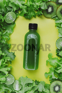 Green juice surrounded by various green fruits and vegetables on yellow, selective focus