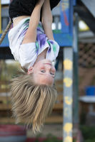 Beautiful little girl hangs upside down on the playground. Little girl smiles into the camera.