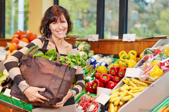 Lächelnde Frau mit Tasche voller Gemüse