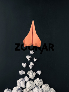 Launching paper rocket with jet stream of paper balls, creativity concept or new ideas metaphor