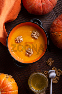 baked pumpkin cream coup with, walnuts ,  coconut milk and natural honey served in nice bowl. served at wooden brown table with ripe orange  pumkins. flat lay. healthy life concept