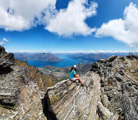 Hiker sits on rocks of The Remarkables mountain range, Queenstown, Otago, South Island, New Zealand,