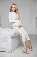 Cute pregnant woman posing in studio