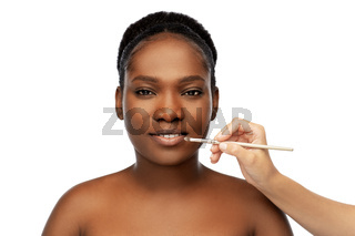 face of african woman and hand with make up brush