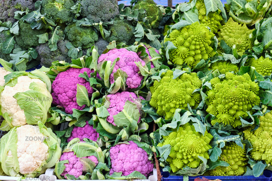 Different kinds of cauliflower and broccoli for sale at a market