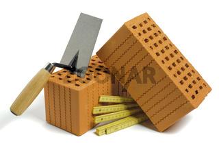 Ziegelsteine und Werkzeug für Hausbau