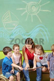 Kinder in Vorschule lesen Buch mit Erzieher