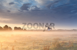windmill in fog at sunrise