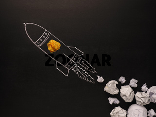 Launching rocket with jet stream of paper balls, creativity concept or new ideas metaphor, start up business