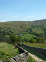 narrow country lane surrounded by stone walls in a west yorkshire dales landscape in the calder valley near hebden bridge
