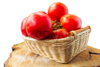 Fresh organic tomatoes with water drops in a basket isolated on white. Close up.