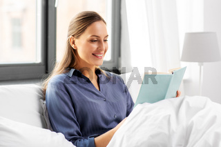 young woman reading book in bed at home