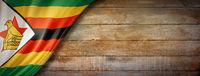 Zimbabwe flag on vintage wood wall banner