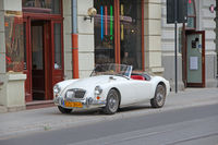 White auto MG cabriolet standing on curb of city road in Lodz
